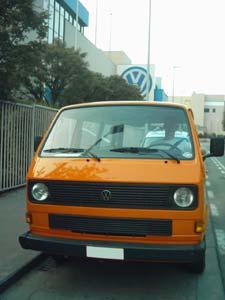 oranje T3 combi met VW reclame op achtergrond