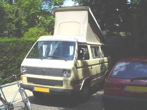VW T3 camper met geopend hefdak en fiets er voor