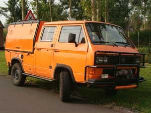 Oranje VW T3 doka Syncro met aluminium opbouw op de laadbak