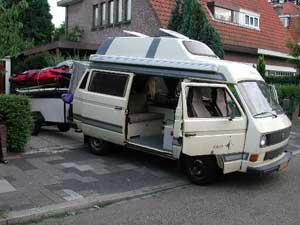VW T3 camper met geopende portieren en een aanhangwagen er achter