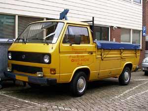Gele VW T3 enkelcabine pick-up met donkerblauw vlakzeil over de laadbak