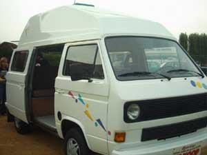 Witte VW T3 camper met kleurige striping op het portier
