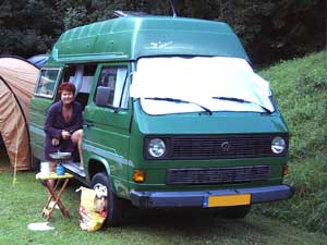 Groene VW T3 Syncro camper met verhoogd dak zonnewering over de voorruit en vrouw in de schuifdeur