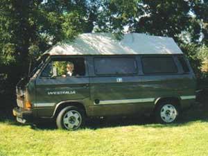 VW T3 camper onder bomen op een grasveld