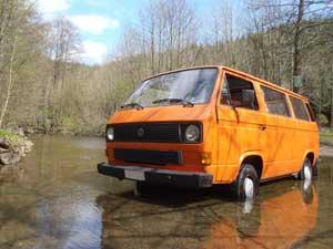 Oranje T3 kombi geparkeerd in een rivier met laag water