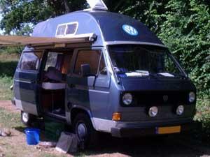 Blauwe camper met hoogdak en uitgezette luifel