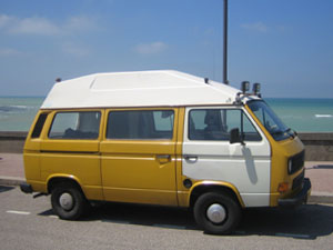 Gele VW camper met wit portier en dak