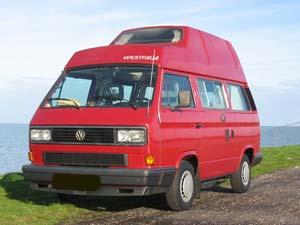 Rode Westfalia camper langs het water