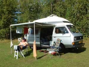 Camper met luifel en kampeermeubelen en zonnebadende persoon