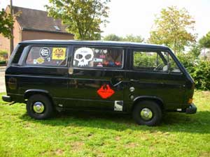 Personenbus zwart met sticker schedel op ruit