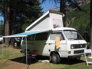 Witte camper met geopend hefdak en uitgezette luifel