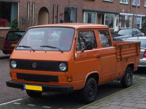 Oranje dubbelcabine pick-up langs de straat
