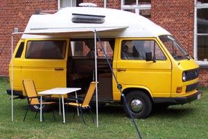 VW T3 camper met uitgezette luifel en tuinmeubelen