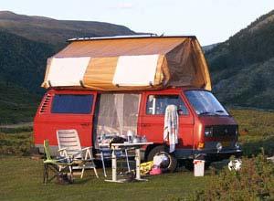 Camper met geopend devon dak in de bergen
