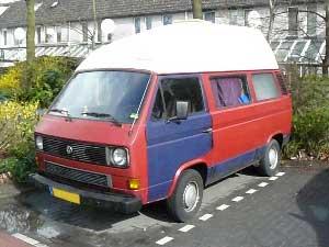 Rode VW camper met blauw portier en wit dak