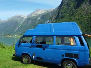 Blauwe T3 camper met reimo dak in bergen landschap