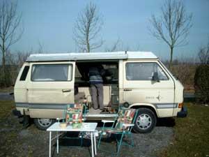 T3 camper met geopende schuifdeur en kampeertafel met stoelen